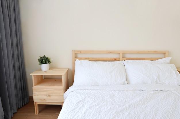 Nuovo letto bianco moderno in camera da letto con luce morbida e chiara Foto Premium