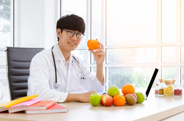 Nutrizionista maschio che si siede allo scrittorio della clinica e che tiene frutta arancio fresca con sorridere. concetto di assistenza sanitaria e dieta. Foto Premium