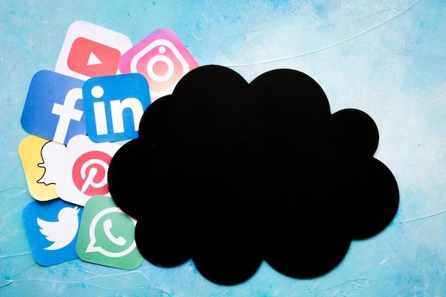 Nuvola di carta nera vicino alle icone dell'applicazione del telefono cellulare sopra fondo blu Foto Gratuite