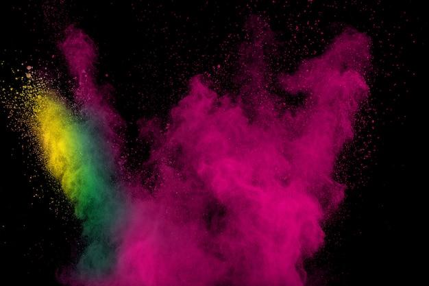 Nuvola di esplosione della polvere di colore su fondo nero. schizzi di particelle di polvere colorata. Foto Premium
