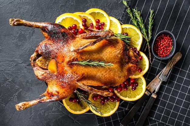 Oca al forno ripiena di arance e rosmarina. tavolo festivo vista dall'alto. Foto Premium