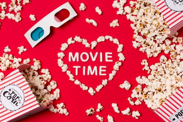 Occhiali 3d; popcorn versato dalla scatola con il testo del film tempo a forma di cuore sul fondale rosso Foto Gratuite