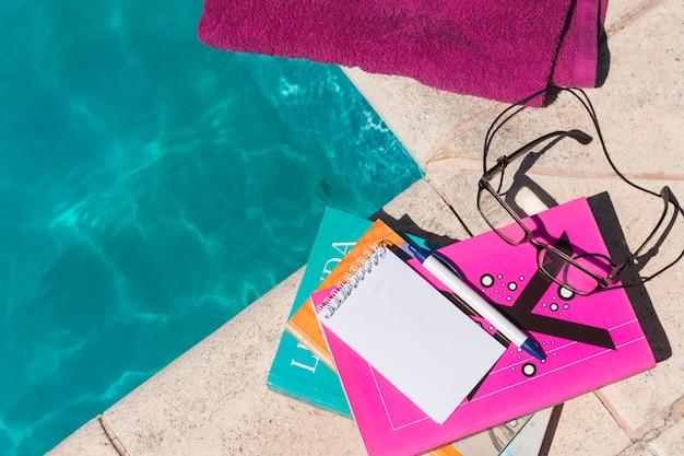 Occhiali con libri e blocco note vicino asciugamano e piscina Foto Gratuite
