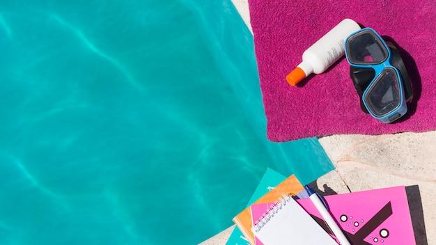 Occhiali con lozione sul telo vicino a libri e piscina Foto Gratuite