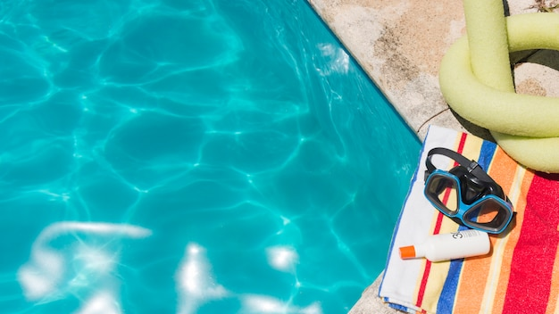 Occhiali con lozione sul telo vicino giocattolo e piscina Foto Gratuite
