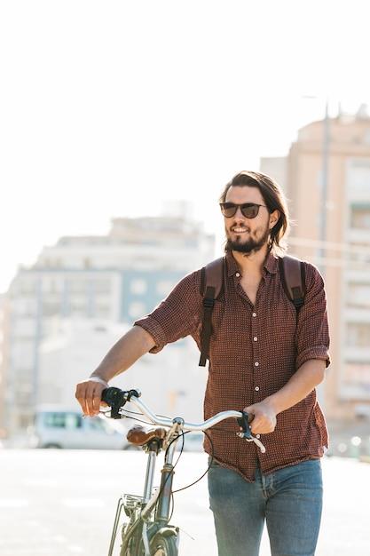 Occhiali da sole d'uso sorridenti del giovane che camminano con la bicicletta sulla strada nel pomeriggio Foto Gratuite