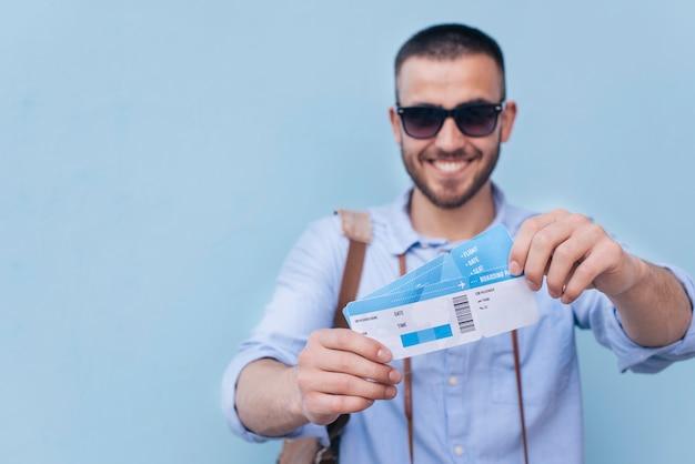 Occhiali da sole da portare sorridenti dell'uomo che mostrano biglietto aereo su priorità bassa blu Foto Gratuite