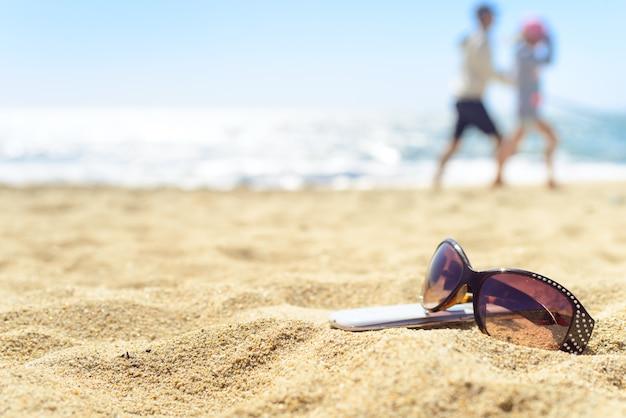 Occhiali Da Sole E Telefono Sulla Spiaggia Con Persone Sullo Sfondo