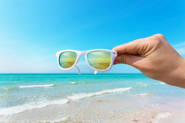 Occhiali da sole in mano sulla spiaggia Foto Premium