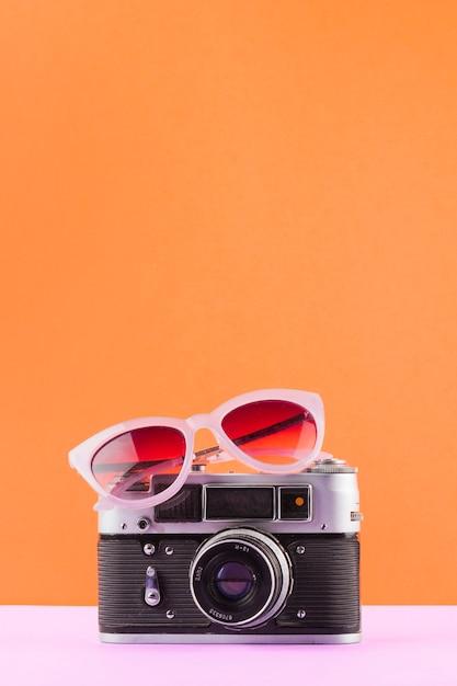 Occhiali da sole sopra la macchina fotografica d'epoca sulla scrivania bianca su uno sfondo arancione Foto Gratuite