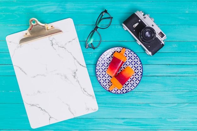 Occhiali e macchina fotografica e supporto e ghiaccioli sul piatto sulla superficie in legno Foto Gratuite