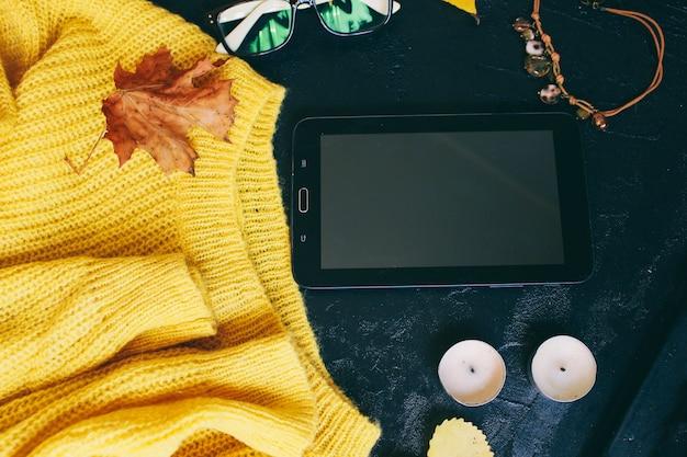 Occhiali e un maglione giallo brillante si trovano su uno sfondo scuro Foto Premium