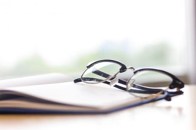 Occhiali neri sul notebook sul tavolo. occhiali lenti. Foto Premium