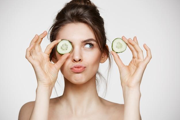Occhio nascondentesi sorridente della giovane bella ragazza nuda dietro la fetta del cetriolo sopra fondo bianco. concetto di bellezza spa e cosmetologia. Foto Gratuite