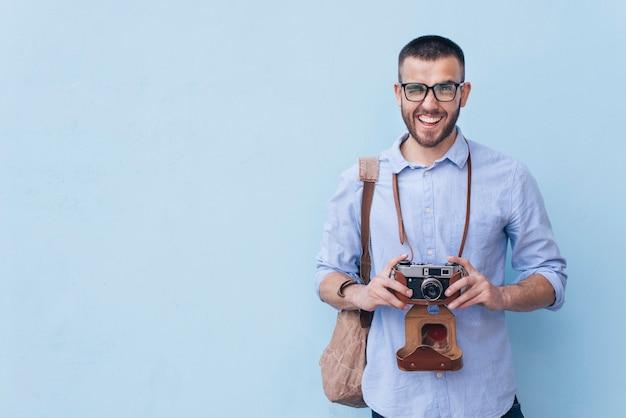 Occhio sbattente le palpebre sorridente dell'uomo mentre tenendo macchina fotografica che sta contro il fondo blu Foto Gratuite