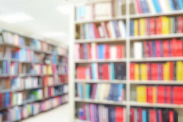 Offuscata dell'interno della biblioteca con libri sugli scaffali. istruzione e concetto di giorno del libro. Foto Premium