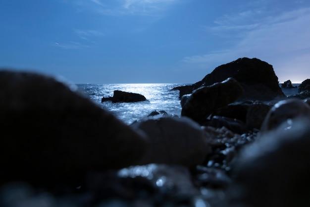 Offuscata rocce nell'acqua di notte Foto Gratuite