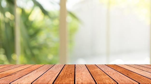 Offuschi la vista del giardino dalla finestra con la luce di mattina con la prospettiva della tavola di legno per fondo Foto Premium