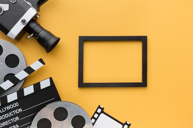 Oggetti cinema piatto laici su sfondo giallo con cornice nera Foto Gratuite