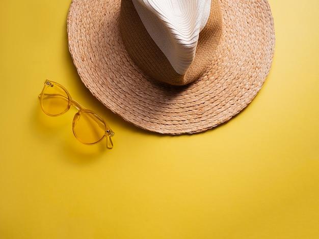 Oggetti sunprotection. il cappello della donna della paglia con i vetri di sole gialli su giallo di vista Foto Premium