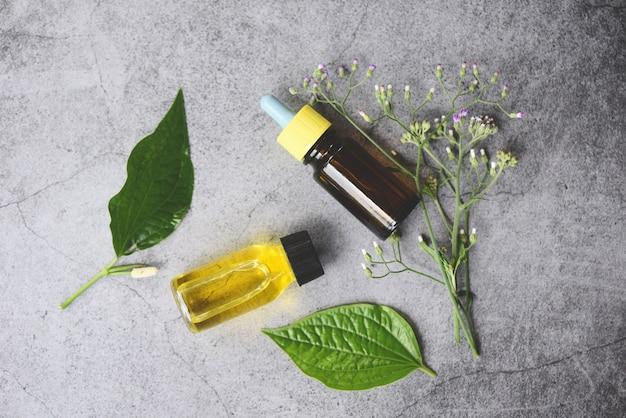 Oli essenziali naturali su foglie di legno e verde biologico - aromaterapia aroma olio di bottiglie di erbe con foglie formulazioni a base di erbe tra cui fiori di campo ed erbe su legno vista dall'alto Foto Premium