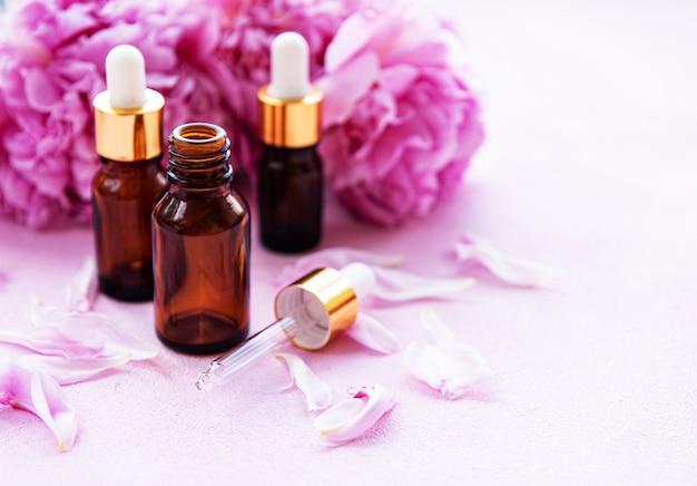Oli essenziali per aromaterapia e peonie rosa Foto Premium