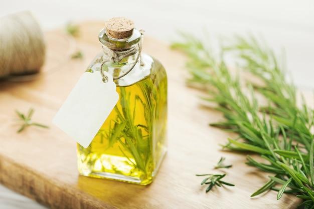Olio alle erbe su bottiglia di vetro con etichetta vuota Foto Premium