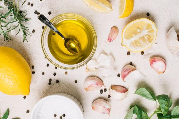 Olio d'oliva di vista superiore del colpo del primo piano circondato cucinando gli ingredienti Foto Gratuite
