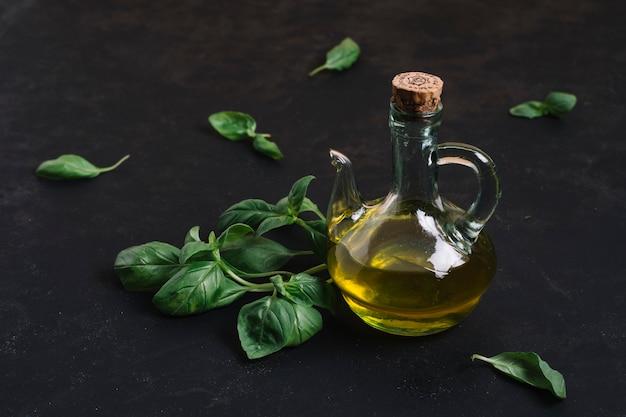 Olio d'oliva in bottiglia con spinaci attorno Foto Gratuite