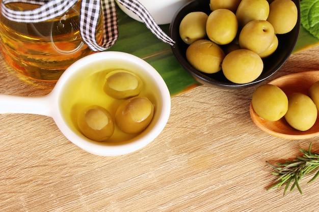 Olio d'oliva per la salute su fondo di legno Foto Premium