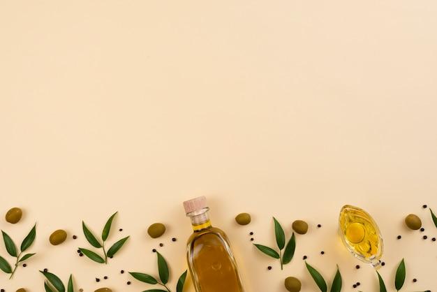 Olio d'oliva su sfondo rosa con spazio di copia Foto Gratuite