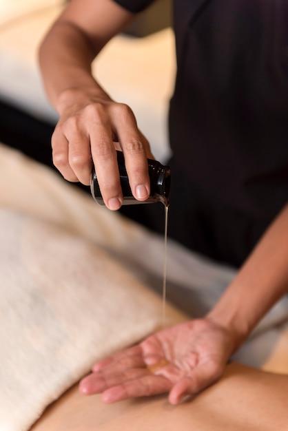 Olio da versare a mano per il massaggio nella spa Foto Premium