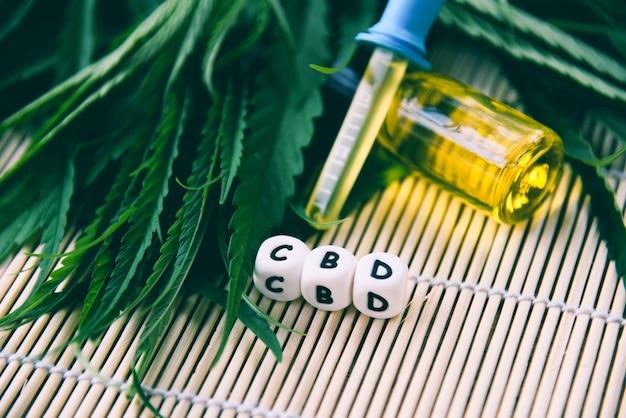 Olio di cannabis in bottiglia prodotti in legno sfondo olio di cannabis foglie di cannabis foglia di marijuana per la canapa assistenza sanitaria medica Foto Premium