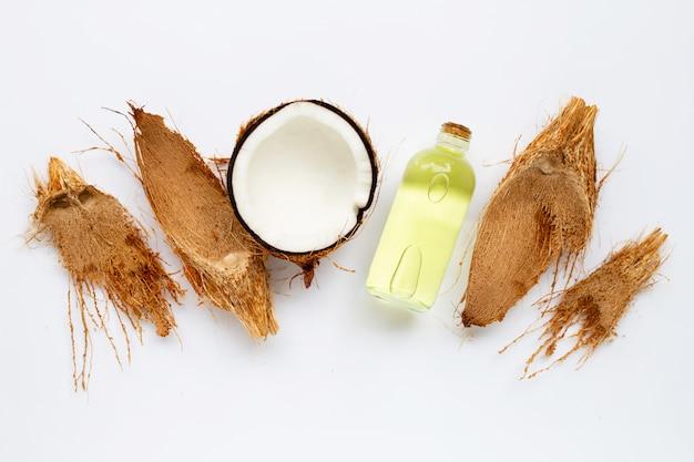 Olio di cocco con le noci di cocco su bianco. Foto Premium