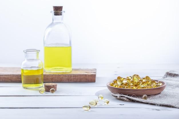 Olio di enotera in capsule e in bottiglie, su una base di legno bianco. concetto di assistenza sanitaria. Foto Premium
