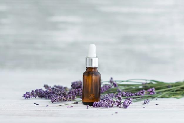 Olio di erbe di lavanda e fiori di lavanda su fondo di legno grigio. Foto Premium