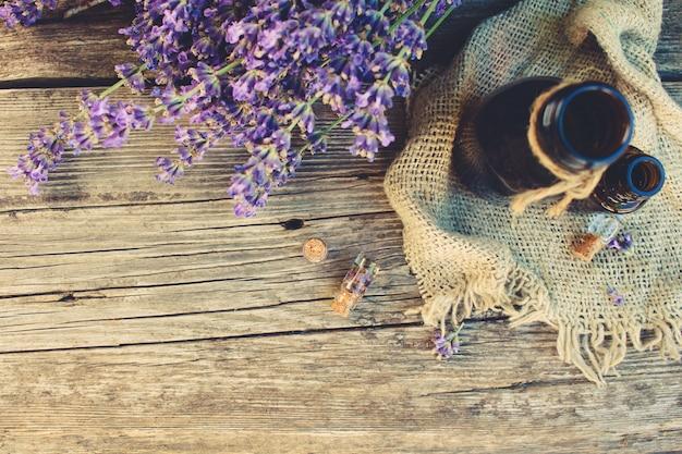 Olio di lavanda in diverse bottiglie su fondo di legno. immagine tonica. vista dall'alto. Foto Premium
