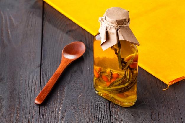 Olio di olivello spinoso in piccole bottiglie. messa a fuoco selettiva Foto Premium