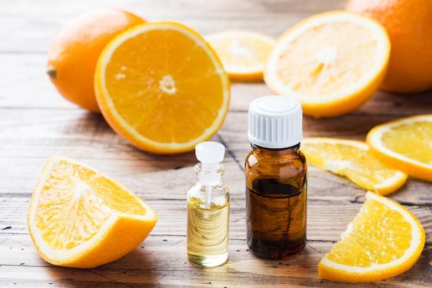 Olio essenziale arancione in bottiglia, fette di frutta fresca su fondo di legno. fragranze naturali Foto Premium