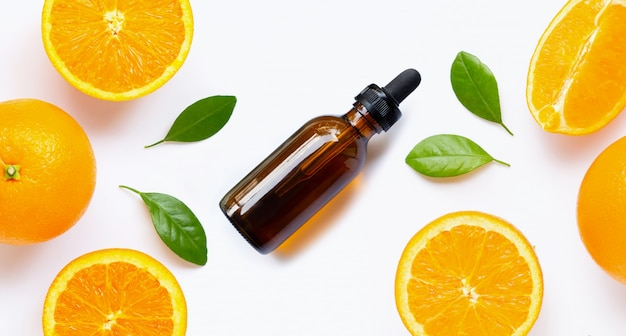 Olio essenziale con agrumi freschi arancioni con foglie isolate on white Foto Premium