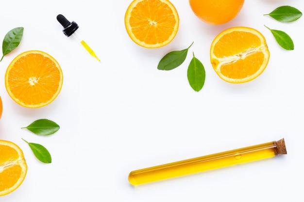 Olio essenziale con agrumi freschi arancioni e foglie isolati su bianco Foto Premium