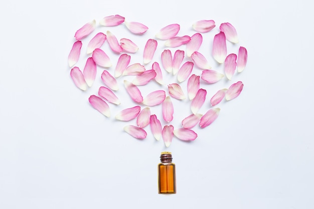 Olio essenziale con petali di loto rosa su bianco Foto Premium