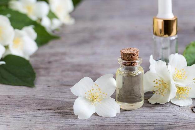 Olio essenziale di gelsomino. massaggi l'olio con i fiori del gelsomino su un fondo di legno Foto Premium