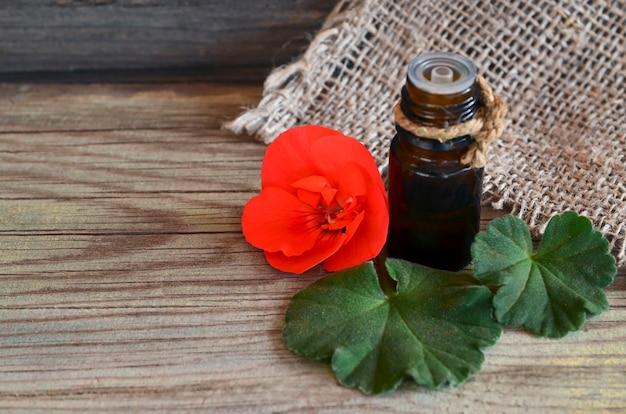 Olio essenziale di geranio in una bottiglia di vetro con fiori e foglie della pianta di geranio. olio di geranio per spa, aromaterapia e cura del corpo. estrarre olio di geranio. Foto Premium