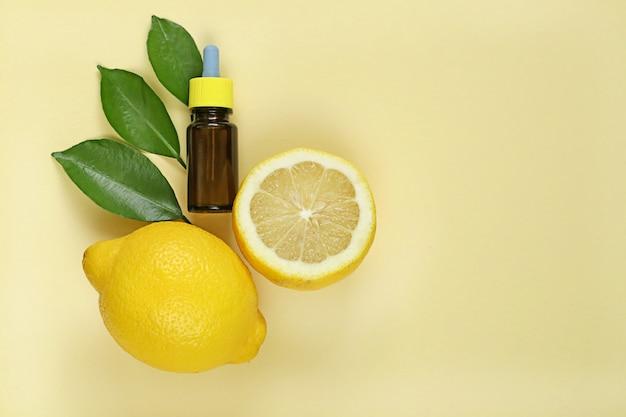Olio essenziale di limone estratto di limone in una bottiglia marrone Foto Premium