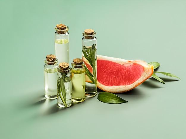 Olio essenziale in bottiglia di vetro con pompelmo fresco e succoso e trattamento di bellezza delle foglie verdi. Foto Gratuite