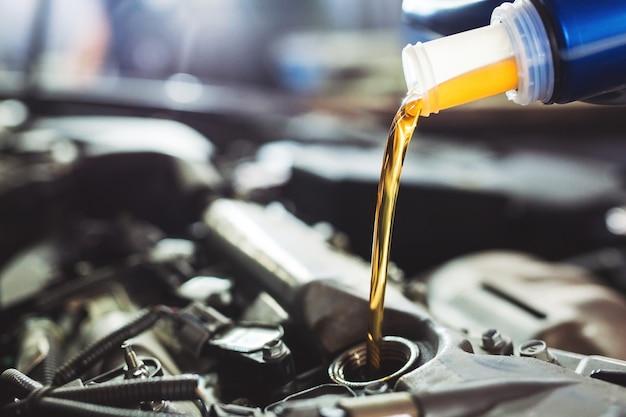 Olio motore versato al motore dell'auto. Foto Premium