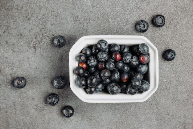 Olive nere di vista superiore in ciotola quadrata su fondo grigio. orizzontale Foto Gratuite