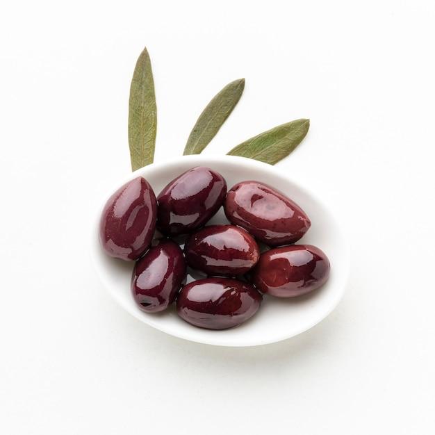 Olive viola sul piatto con foglie Foto Gratuite