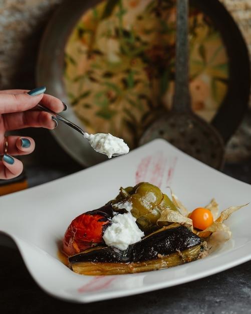 Olma di verdure tradizionale in un piatto bianco con yogurt Foto Gratuite